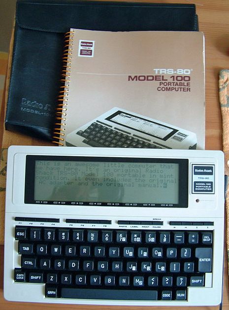 TRS-80 Model 100 with manual - looks like a book turned sideways, with a keyboard at the bottom, and a smallish LCD multi-line display at the top.